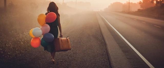 mujer-caminando-por-carretera-con-maleta-y-globos-720x300